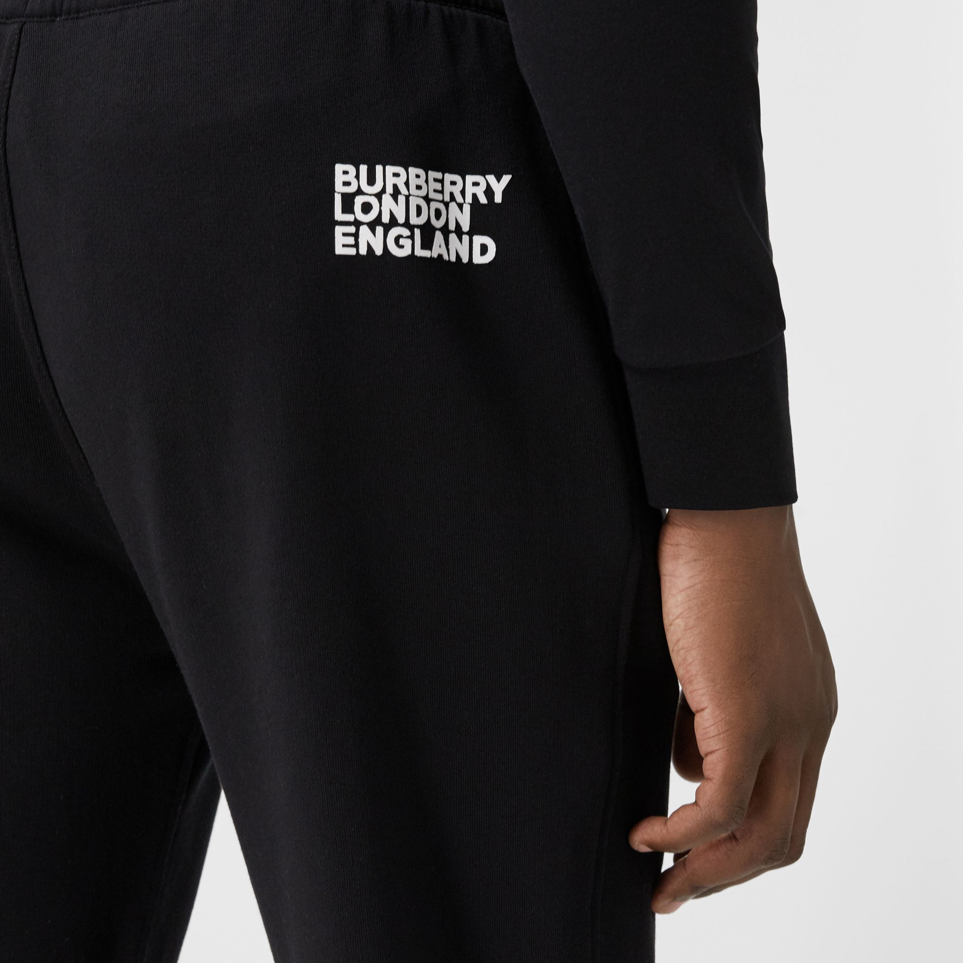 Love Print Cotton Jogging Pants in Black - Men | Burberry - gallery image 1