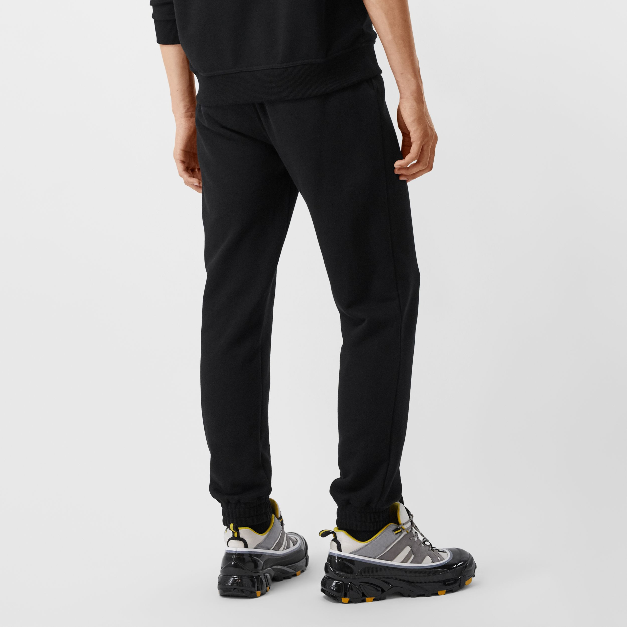 Monogram Motif Cotton Jogging Pants in Black - Men | Burberry Australia - 3