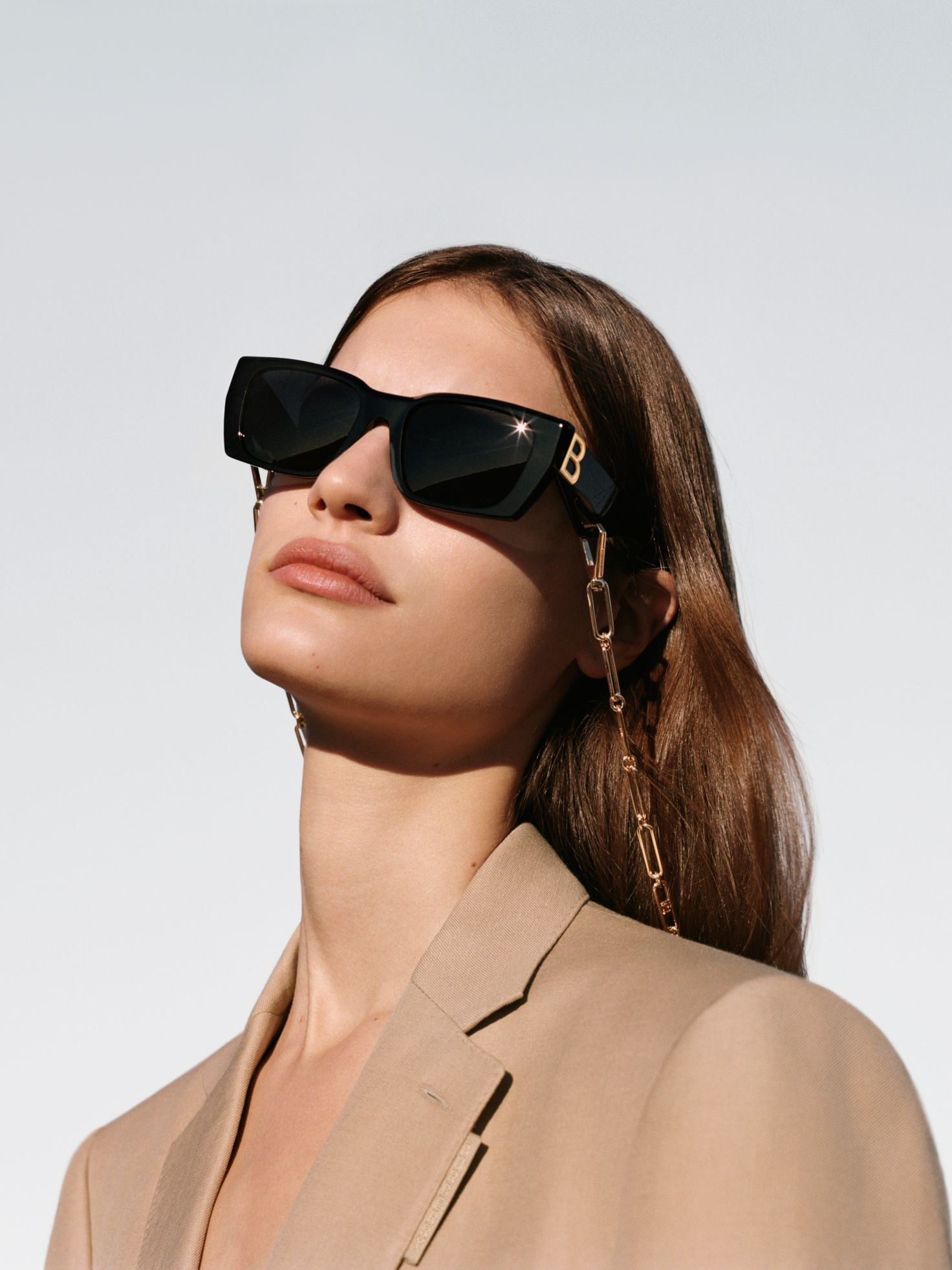 model wearing black square frames with chain