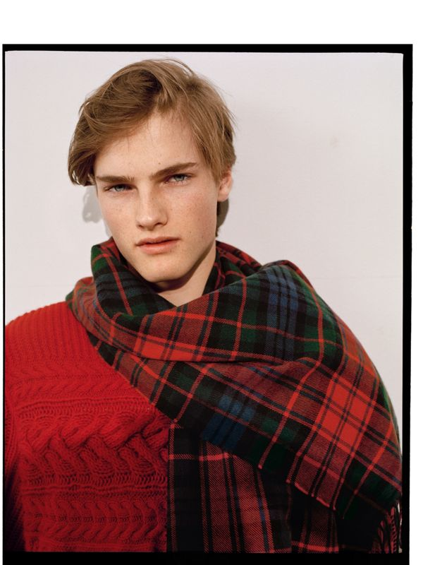 Hugo wears a textured tartan scarf draped for nonchalance.