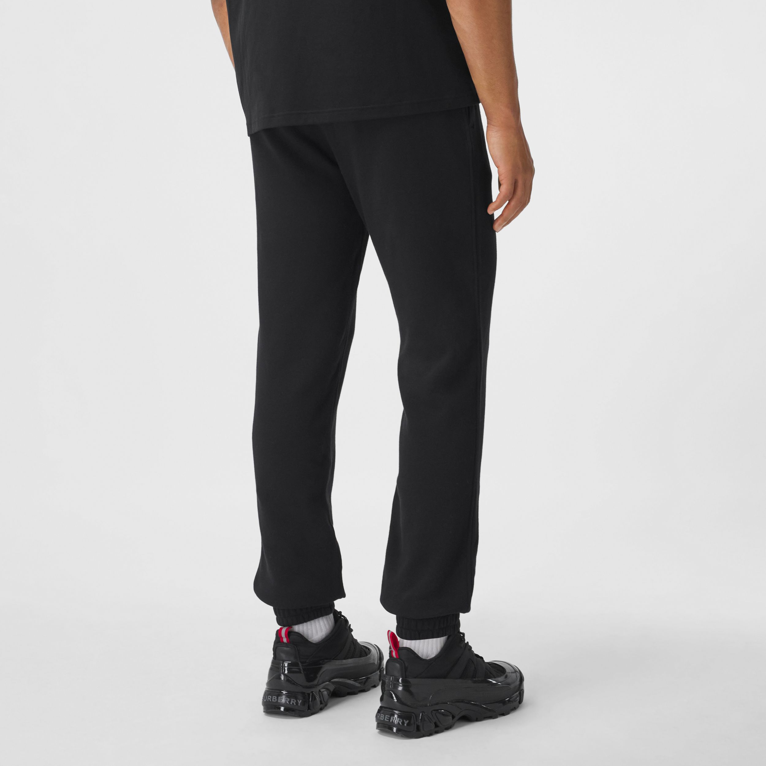 Logo Graphic Appliqué Cotton Jogging Pants in Black - Men | Burberry Canada - 3